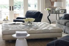 14 an oversized tufted ottoman adds a refined touch to the space and works as a coffee table