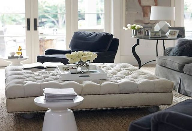 an oversized tufted ottoman adds a refined touch to the space and works as a coffee table