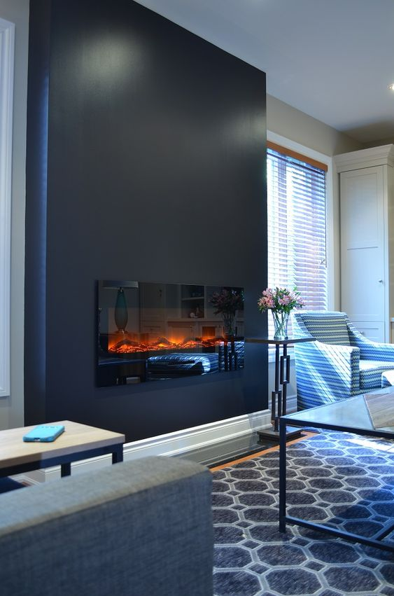 a black accent wall with a built-in fireplace for a cozier feel