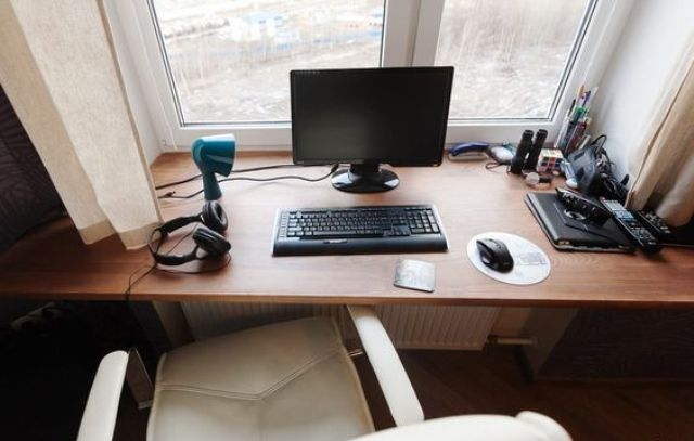 a small working space on the windowsill and a comfy white leather chair