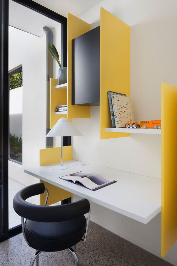 a colorful modern workspace with a floating desk and some colorful geometric shelves