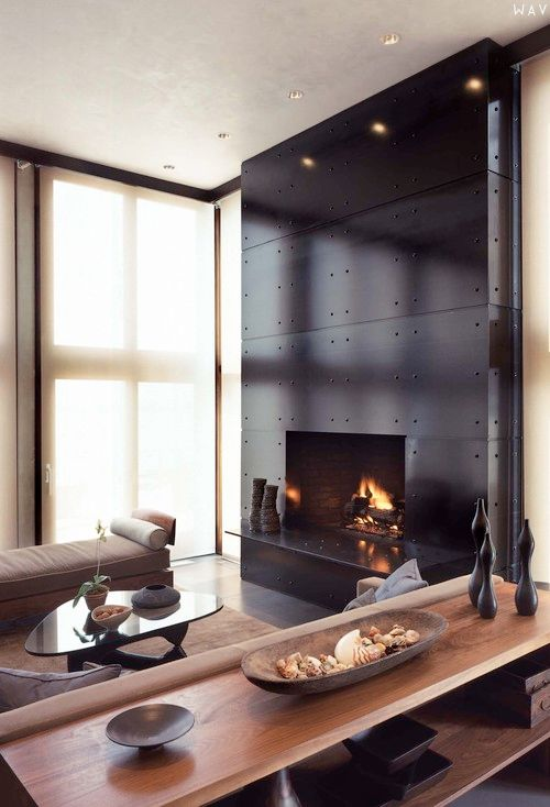 a fireplace accentuated with black metal panels looks chic and a bit industrial