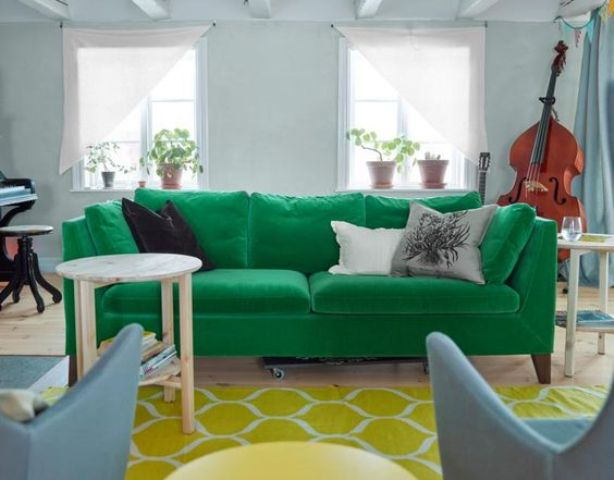 an emerald Stockholm sofa, a yellow rug and powder blue chairs add color to the space and make it bold