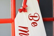 16 large handmade door tags instead of a traditional wreath is a bold idea