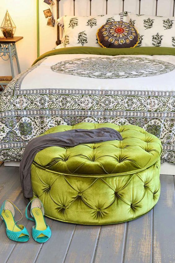 a large green grass upholstered ottoman provides storage and works as a bedroom bench