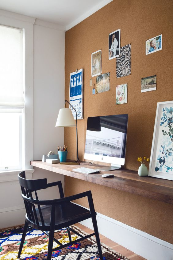 a cork wall and a floating wooden desk that matches the wall is a great combo