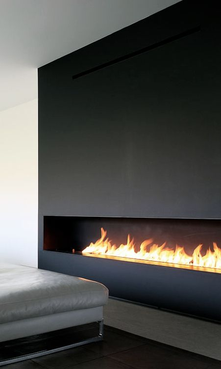a long, horizontal fireplace clad with dark metal looks ultra-minimalist
