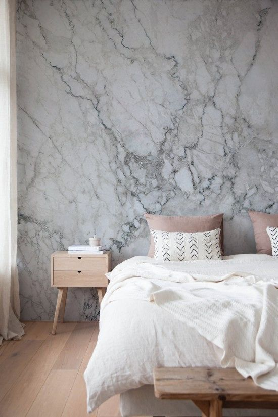 a marble wallpaper headboard wall keeps the space relaxing yet interesting