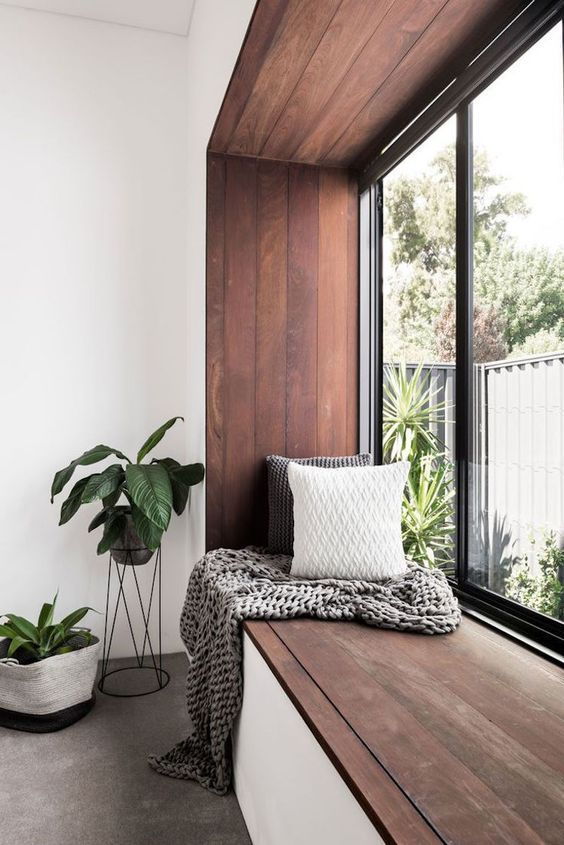 a windowsill covered with dark stained wood is a great seat or daybed