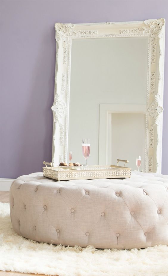 an oversized creamy ottoman plus a large vintage mirror add glam to the bedroom