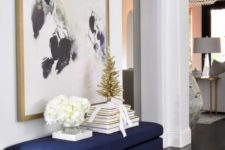 22 an oversized artwork plus a matching navy and gold entryway bench are a chic combo