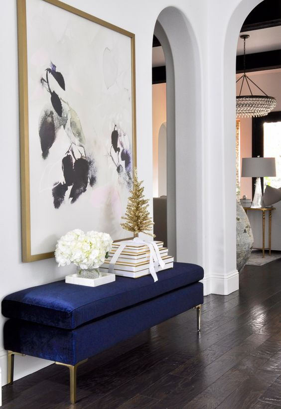 an oversized artwork plus a matching navy and gold entryway bench are a chic combo