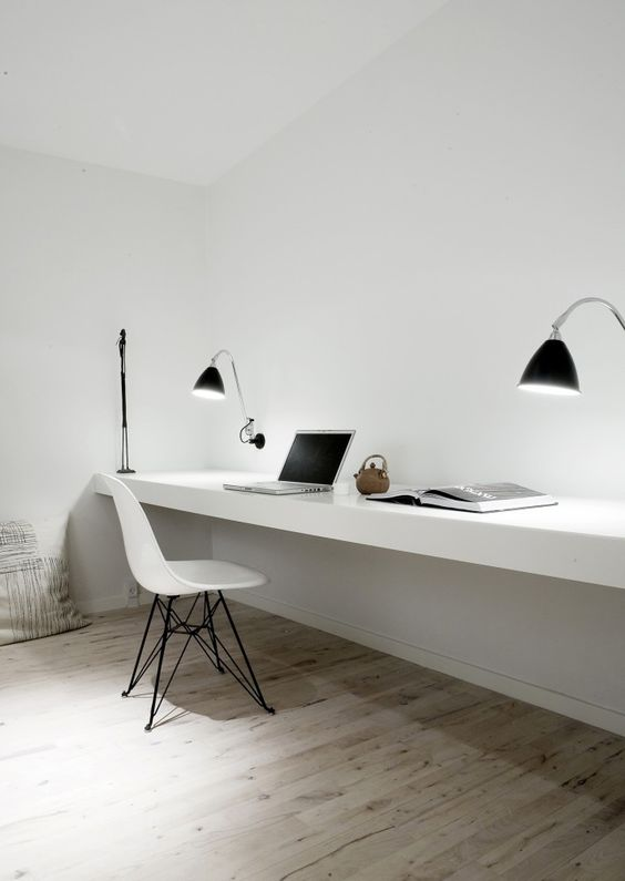 a minimalist workspace with a floating desk, lamps and a modern chair