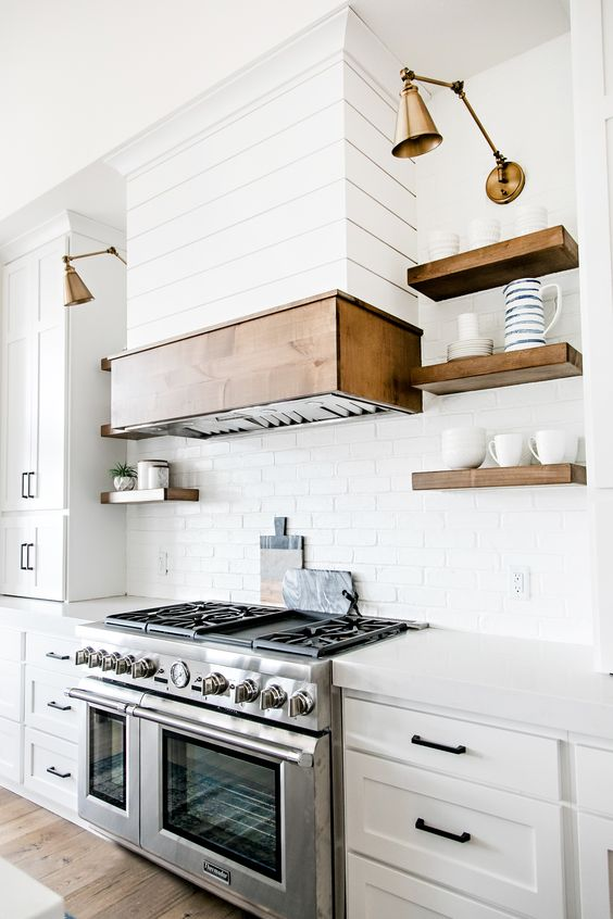 a stainless steel cooker and some brass lamps are nicely paired in the kitchen