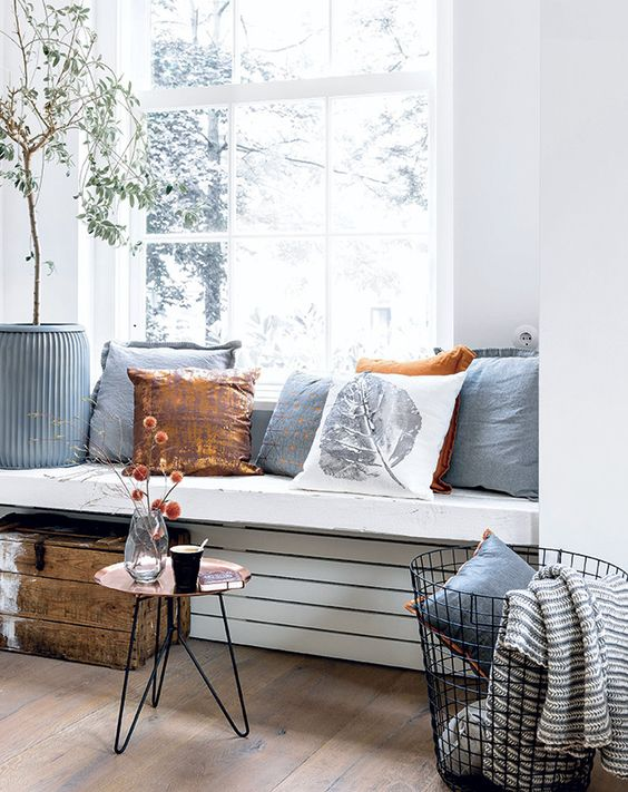 a thick windowsill seat with lots of pillows and a coffee table by its side