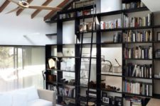 23 the ceiling is acctuated with faux beams and a large and tall bookcase