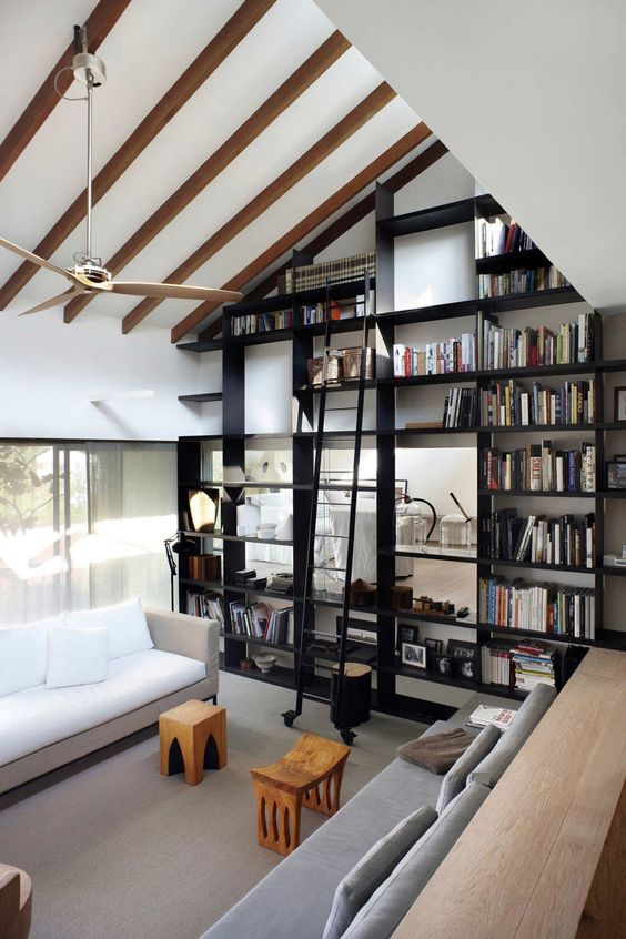 the ceiling is acctuated with faux beams and a large and tall bookcase