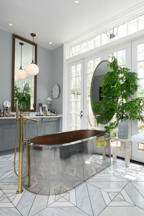 a large metal tub is the main eye-catcher in this bathroom, and brass touches make it cozier