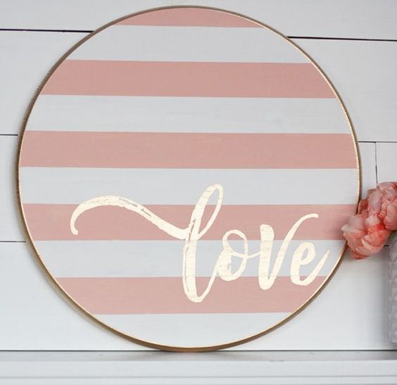 a striped blush and white wooden sign with gold calligraphy