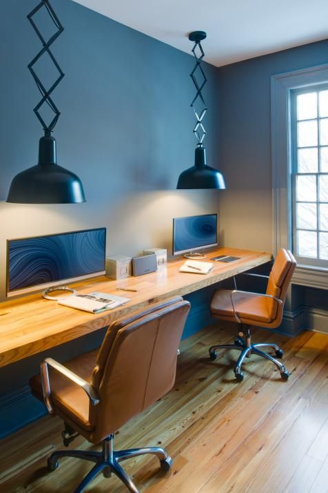 a shared workspace with a floating desk and a couple of leather chairs on casters for comfy working