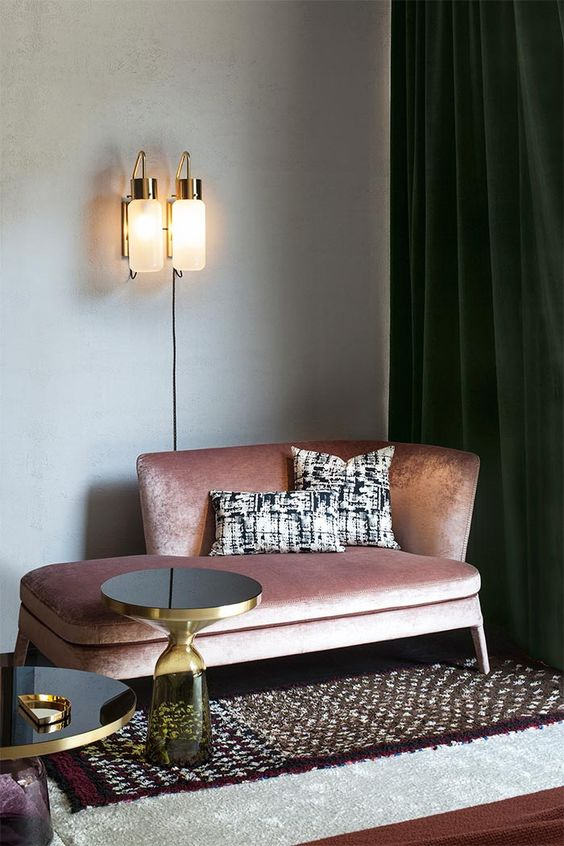 a shiny pink daybed looks very refined and is highlighted with gold rim side tables