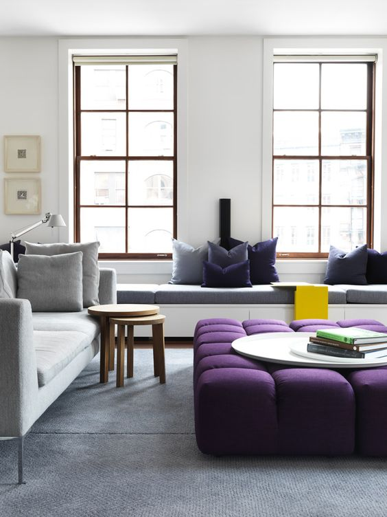 an oversized upholstered purple ottoman spruces up the neutral space and adds a touch of color