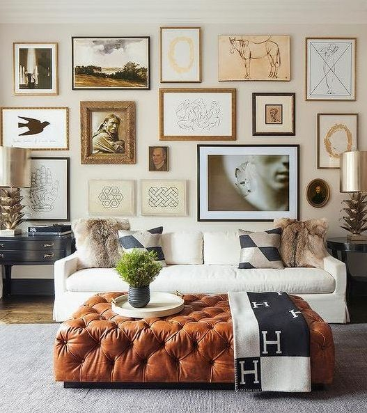 a large brown leather ottoman brings a touch of color and texture to this living room