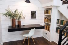 26 a small attic workspace with a dark-stained floating desk and built-in bookshelves