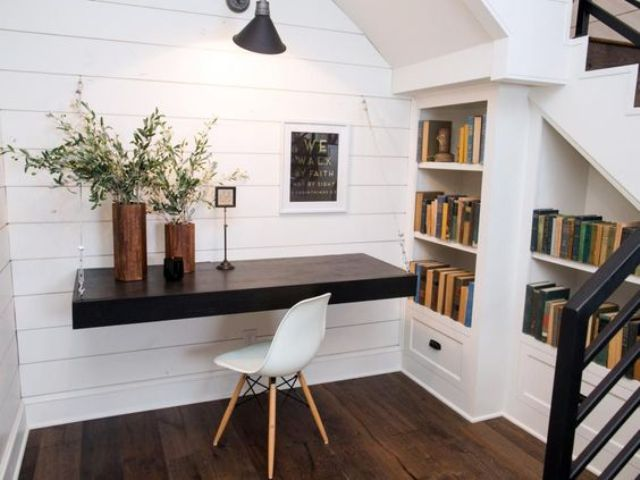 a small attic workspace with a dark stained floating desk and built in bookshelves