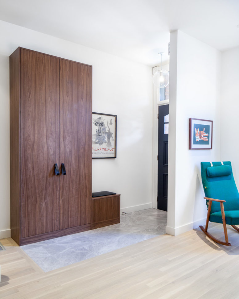 Custom walnut panels and doors and leather pulls turn narrow depth wardrobes into a luxorious storage solution for an entryway. (Wanda Ely Architect Inc.)