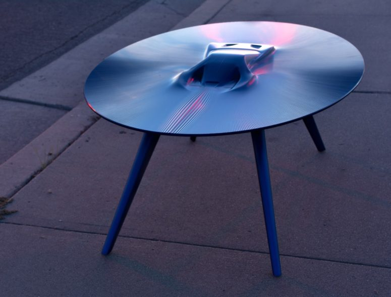 Bold Ford GT table features a vehicle that seems to be appearing from liquid metal in the center of the table