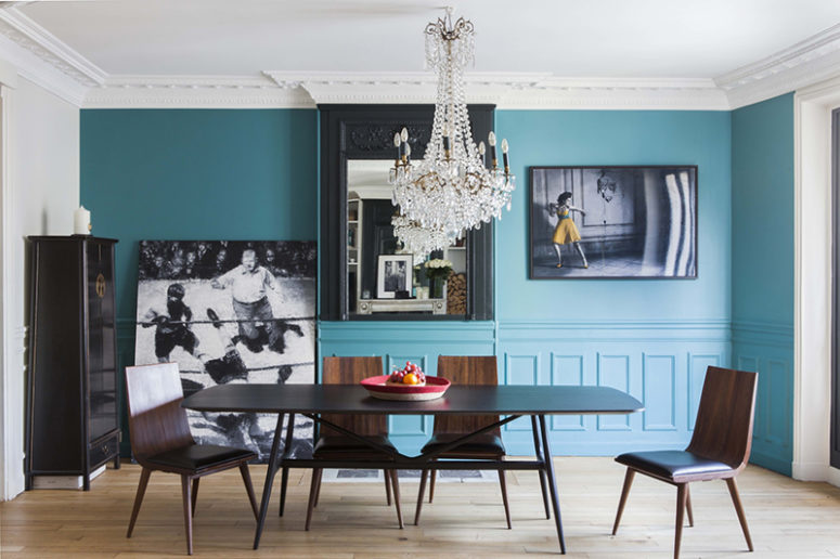 The dining room is done with blue walls, a mid century modern dining set, a glam crystal chandelier and amazing artworks
