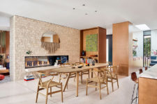01 The dining space features a faux brick wall with a double-sided fireplace and a light-colored wooden dining set
