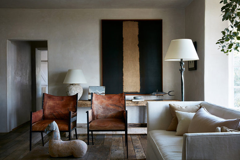 The living room is done in neutrals, with some leather chairs, a gorgeous statement artwork, a unique statuette