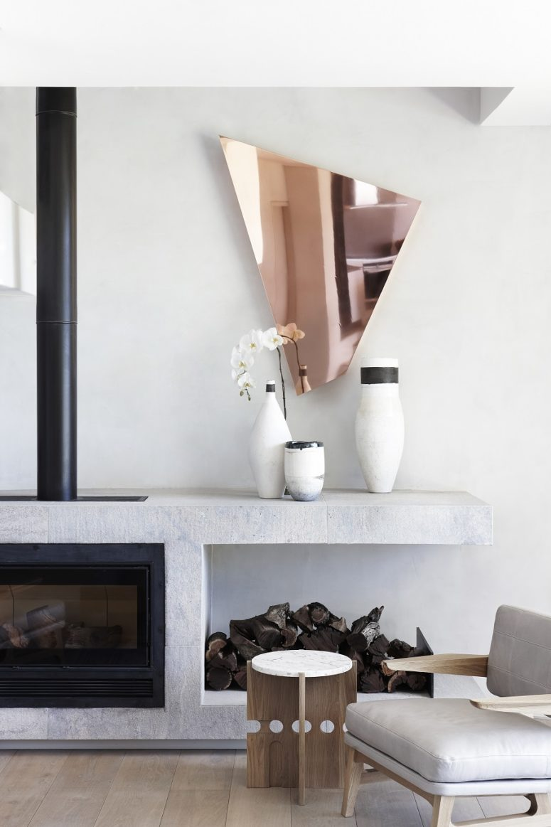 Here's a hearth, a copper mirror and firewood storage that adds coziness to the space