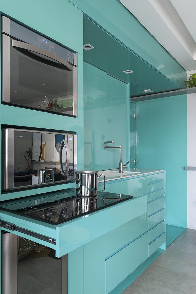 Sleek green surfaces make the kitchen stand out and visually separate this utility zone from the rest of the space
