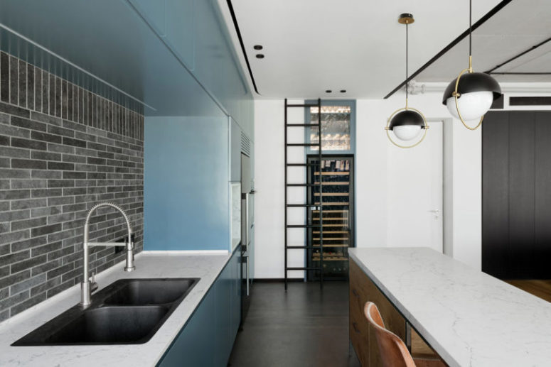 The kitchen includes blue cabinet, a large wine cooler and a kitchen island with a breakfast space