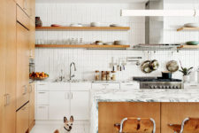 02 The kitchen united with the dining space is filled with light, done with white tiles and cabinets and some marble