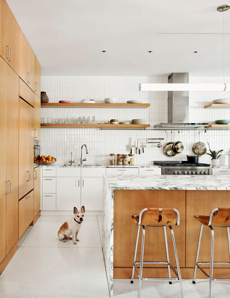 The kitchen united with the dining space is filled with light, done with white tiles and cabinets and some marble