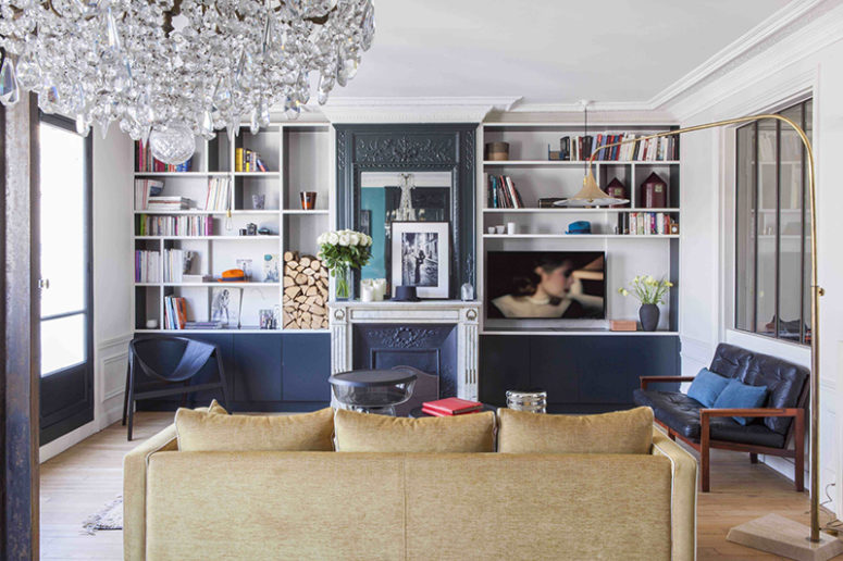 The living room is done with black ana navy touches, a faux fireplace, built-in storage shelves and eye-catchy furniture