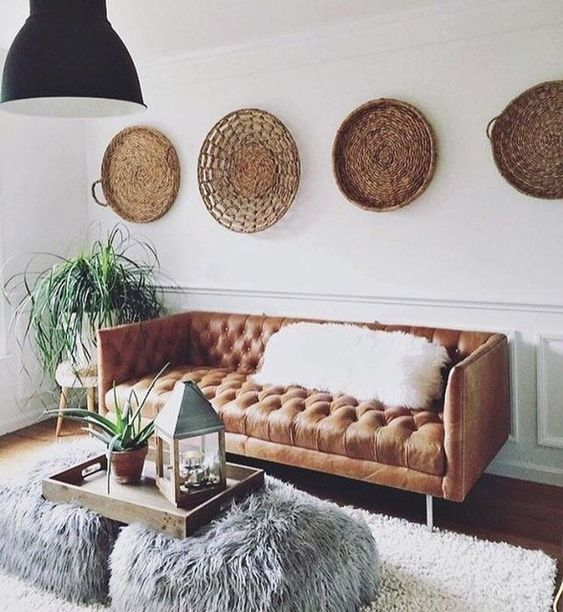 a boho space with an amber leather Chesterfield and baskets on the walls