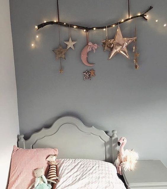a branch with stars and half moons and string lights for cherring up the sleeping nook