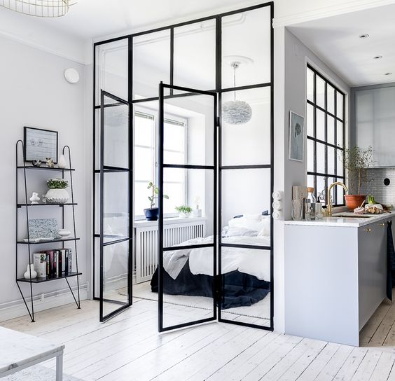 a cozy bedroom with glass framed walls to separate it from the kitchen and make it more private