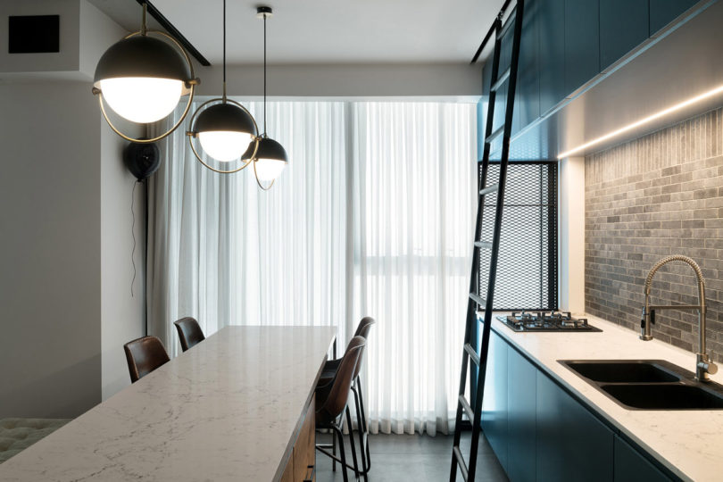 A brick backsplash and pendant lamps plus leather chairs add an industrial touch