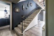 03 The hallway features an original marble staircase and a black wall plus some vintage mirrors