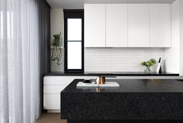 The kitchen is done with white cabinets and black stone countertops, the backsplash is of white brick