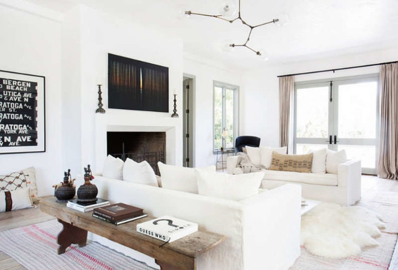 The living room is a gorgeous large space filled with whites and light, a fireplace and some rustic touches that add coziness