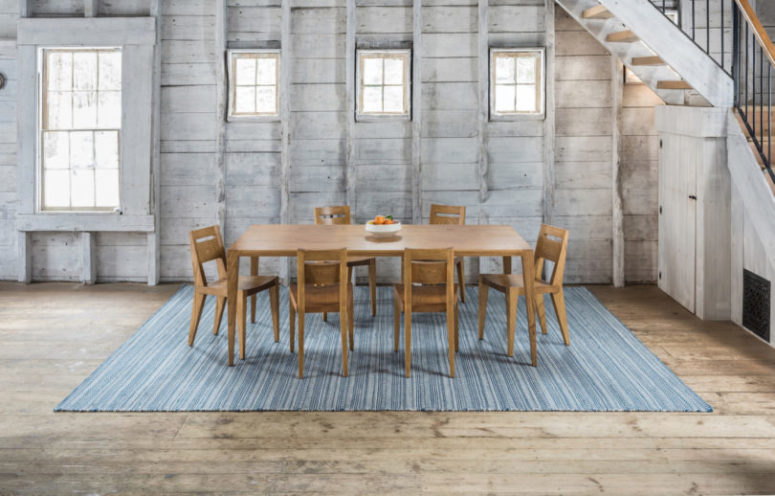 Tula dining table and chairs on the Amma area rug that features blue stripes