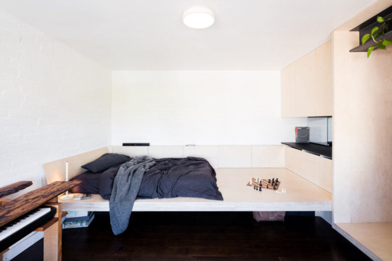 White walls make the space larger, and light-colored plywood continues with this idea while adding texture