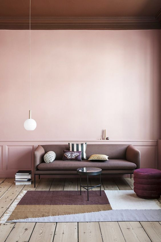 a chic pastel space with a blank pink wall that makes the space balanced